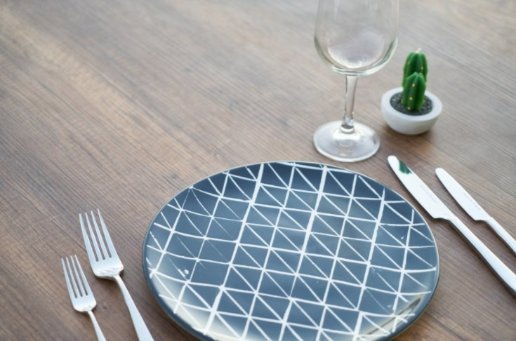 round-blue-and-white-ceramic-plate-two-forks-two-knives-and-wine-glass